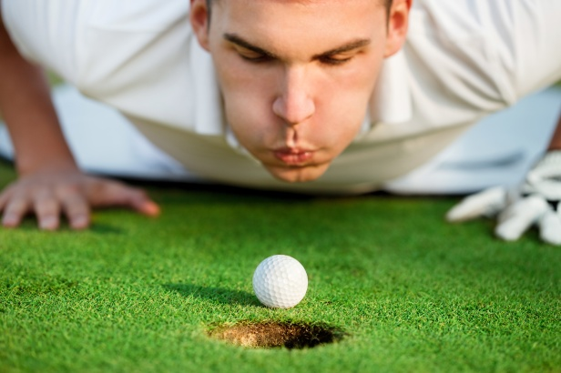 golfer blowing in the ball